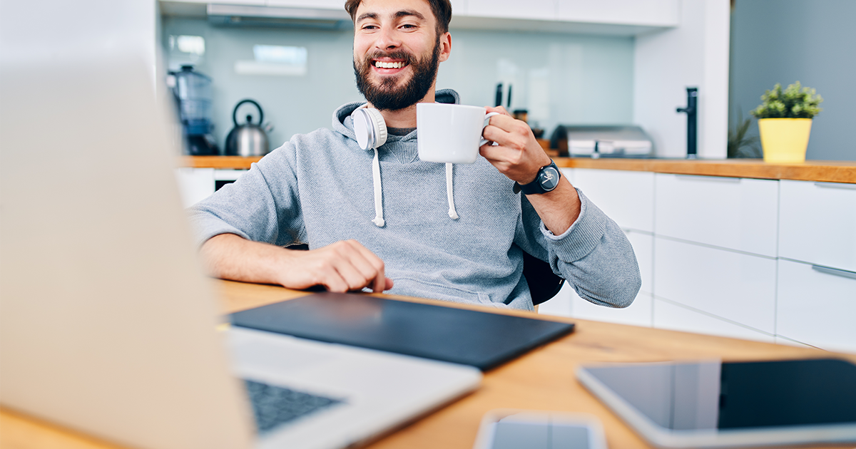 Man with coffee mug looking at a laptop