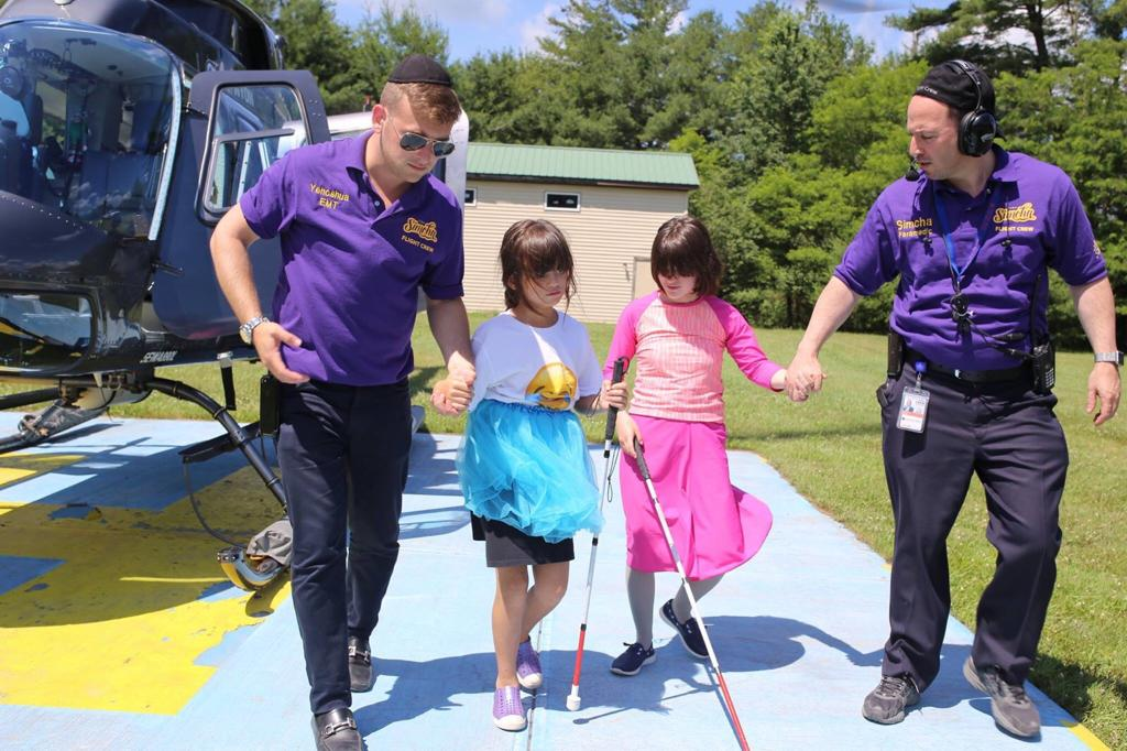 Children with disabilities debarking a helicopter